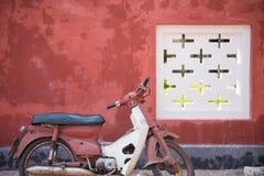 有红色墙壁的老摩托车 免版税库存照片