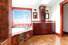 有红色大理石和桃花心木木头的豪华新的家庭卫生间。 免版税库存图片