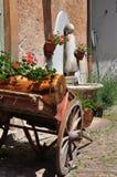 有红色大竺葵和喷泉的老木运输车 免版税库存图片
