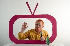 有红色头发、一个胡子和一根髭的一个人在一件黄色衬衣,玻璃模仿在电视上的总统` s讲话 圣诞节, Ne 免版税图库摄影