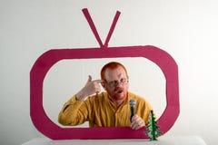 有红色头发、一个胡子和一根髭的一个人在一件黄色衬衣,玻璃模仿在电视上的总统` s讲话 圣诞节, Ne 免版税库存照片