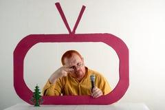 有红色头发、一个胡子和一根髭的一个人在一件黄色衬衣,玻璃模仿在电视上的总统` s讲话 圣诞节,新 库存照片
