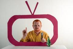 有红色头发、一个胡子和一根髭的一个人在一件黄色衬衣,玻璃模仿在电视上的总统` s讲话 圣诞节, Ne 免版税库存图片