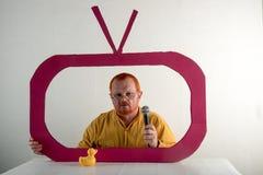 有红色头发、一个胡子和一根髭的一个人在一件黄色衬衣,玻璃模仿在电视上的总统` s讲话 圣诞节, Ne 库存照片