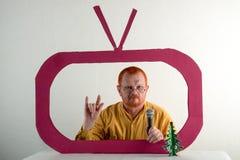 有红色头发、一个胡子和一根髭的一个人在一件黄色衬衣,玻璃模仿在电视上的总统` s讲话 圣诞节, Ne 库存图片