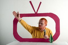 有红色头发、一个胡子和一根髭的一个人在一件黄色衬衣,玻璃模仿在电视上的总统` s讲话 圣诞节, Ne 图库摄影