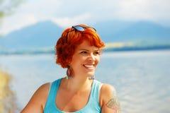 有红色头发和五颜六色的成套装备的美丽的光芒四射的女孩在湖旁边 免版税库存图片