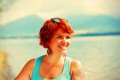有红色头发和五颜六色的成套装备的美丽的光芒四射的女孩在湖旁边 免版税库存照片