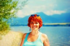 有红色头发和五颜六色的成套装备的美丽的光芒四射的女孩在湖旁边 库存图片