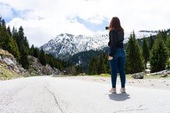 有红色头发摄影师的美丽的年轻女人拍一个山风景的照片在电话的,当远足时 免版税图库摄影