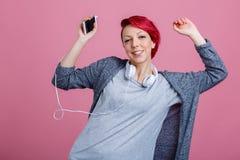 有红色头发的一个女孩听到在耳机和舞蹈的音乐 免版税库存照片