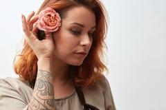 有红色头发的一个美丽的女孩装饰她的有一朵桃红色花的头发,在灰色背景 免版税图库摄影