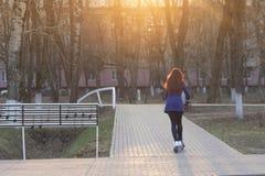 有红色头发的一名年轻白种人妇女在一件蓝色外套在公园快速滚动或乘坐一辆蓝色电滑行车 Eco 免版税库存照片