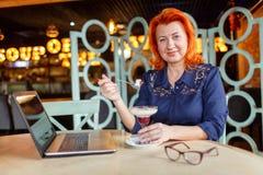 有红色头发的一名美丽的妇女,吃一个点心 户内在咖啡馆 免版税图库摄影