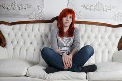 有红色头发的俏丽的女孩盘着腿蹲 库存图片