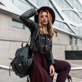 有红色头发的典雅的年轻女人在有一个皮革背包的一件黑夹克在有海角的时髦裤子在腰部坐 库存照片