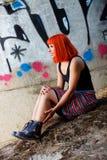 有红色头发的可爱的女孩在街道 免版税库存图片