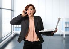 有红色头发的女商人在工作微笑与便携式计算机谈话的繁忙在手机 库存图片