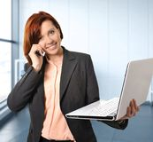 有红色头发的女商人在工作微笑与便携式计算机谈话的繁忙在手机 免版税库存照片