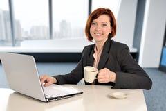 有红色头发的女商人在工作微笑在便携式计算机书桌和饮用的咖啡上的 库存图片