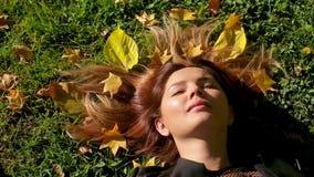 有红色头发的女孩在草说谎并且拿着下落的黄色秋叶在公园 股票视频