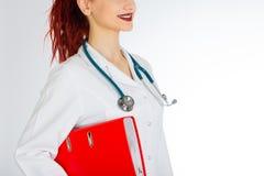 有红色头发的女性医生 奶油被装载的饼干 听诊器文件和白色制服 免版税库存照片