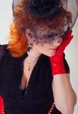 有红色头发的妇女在黑帽会议 库存图片