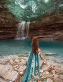 有红色头发的孤独的女孩坐在湖岸的光秃的岩石在马尔特维利峡谷,有性感长的夫人盐水湖露出 库存图片
