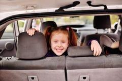 有红色头发的小逗人喜爱的女孩微笑对汽车内部的背景的 图库摄影