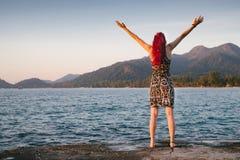 有红色头发的少妇在有山和森林的海洋附近接受美妙的自然 库存照片