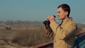 有红色头发的年轻人在看通过从桥梁的双筒望远镜的卡其色的外套 股票录像