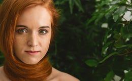 有红色头发的年轻女人在作为围巾的脖子上 库存图片