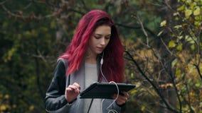 有红色头发的年轻美丽的妇女在秋天公园走并且听到音乐通过片剂个人计算机 有吸引力的妇女年轻人 股票视频