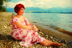 有红色头发的美丽的光芒四射的女孩和五颜六色的sommer在湖旁边穿戴 免版税图库摄影