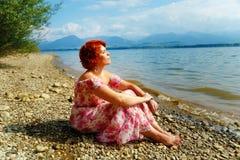 有红色头发的美丽的光芒四射的女孩和五颜六色的sommer在湖旁边穿戴 免版税库存照片