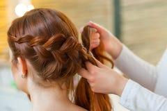 有红色头发的美丽的女孩,美发师编织一个辫子特写镜头,在美容院 库存图片