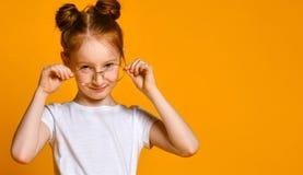 有红色头发的美丽的少女用在她时髦的玻璃的一个百吉卷看您框架的 免版税图库摄影