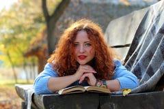 有红色头发的美女在与书和黄色叶子的一条长凳说谎并且调查照相机 秋天公园Backgroun 免版税库存照片