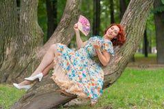 有红色头发的迷人的女孩在摆在有一个爱好者的葡萄酒礼服的减速火箭的样式在她的在一棵树的手上在公园 库存照片