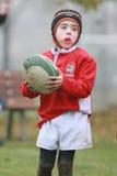 有红色夹克作用橄榄球的男孩 免版税库存图片