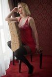 有红色娃娃摆在坐椅子的女用贴身内衣裤和黑长袜的可爱和性感的白肤金发的妇女在窗口附近 免版税库存照片