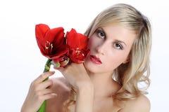 有红色孤挺花花的美丽的白肤金发的女孩在白色 免版税库存照片