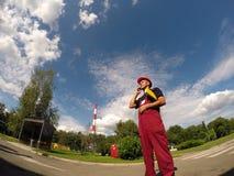 有红色安全帽的产业工人使用手机 免版税库存照片