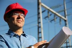 有红色安全帽的在输电线下的工程师和图纸。 免版税库存图片
