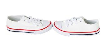 有红色小条的白色帆布鞋 免版税库存照片