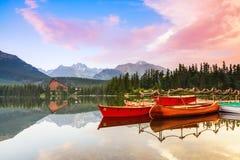 有红色小船和独木舟的不可思议的湖 免版税库存照片