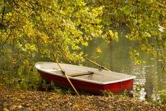 有红色小船的秋天公园在池塘 免版税库存照片