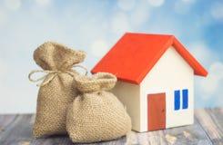 有红色屋顶的一个家在与袋子的绿色背景从有美元的符号的在出售或购买家里面的袋子概念的大袋和金钱 库存照片