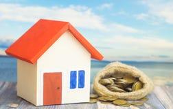 有红色屋顶的一个家在与袋子的蓝色背景从有硬币金钱的大袋在出售或购买家里面的概念 库存照片