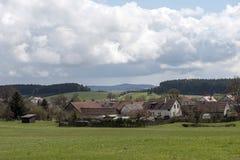 有红色屋顶的一个小村庄在领域和森林中间 库存图片